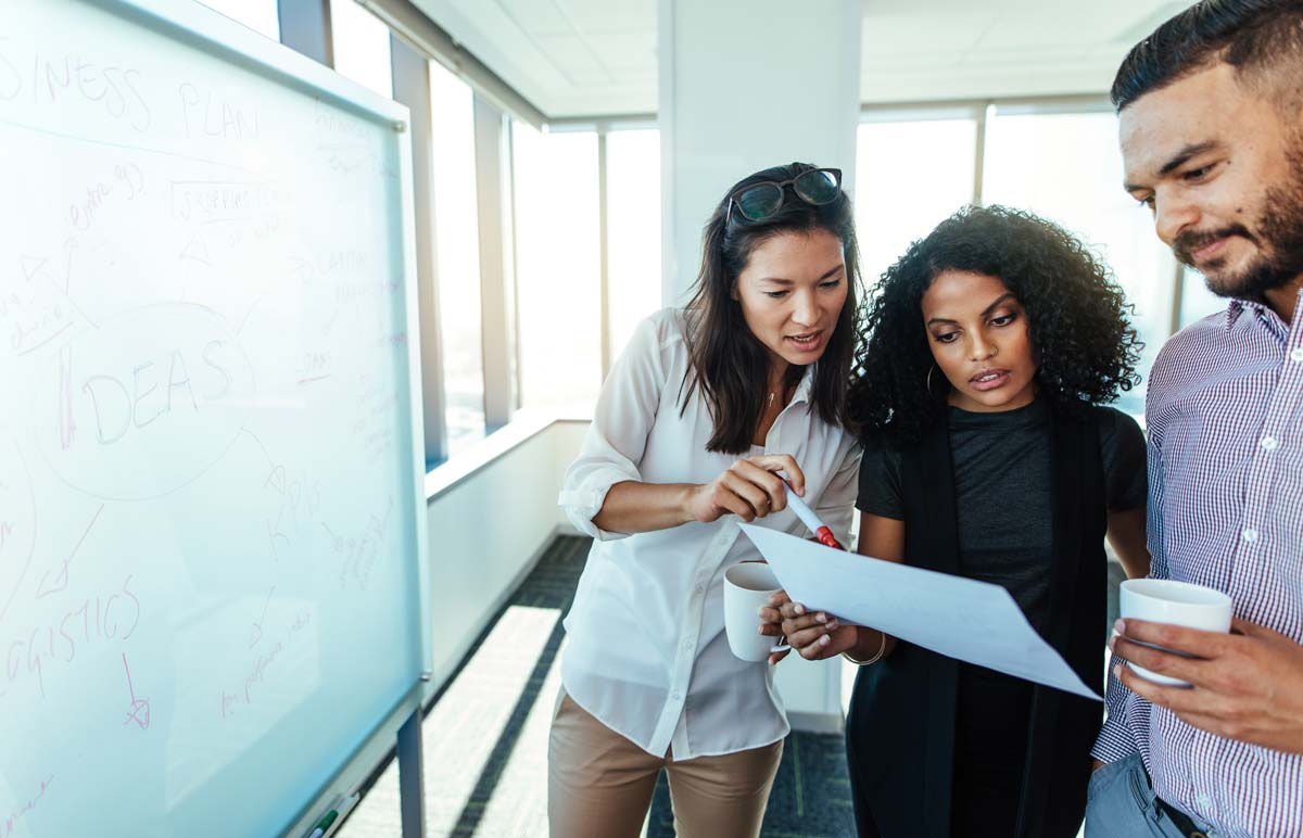three co-workers studying sheet of paper reviewing AP processes